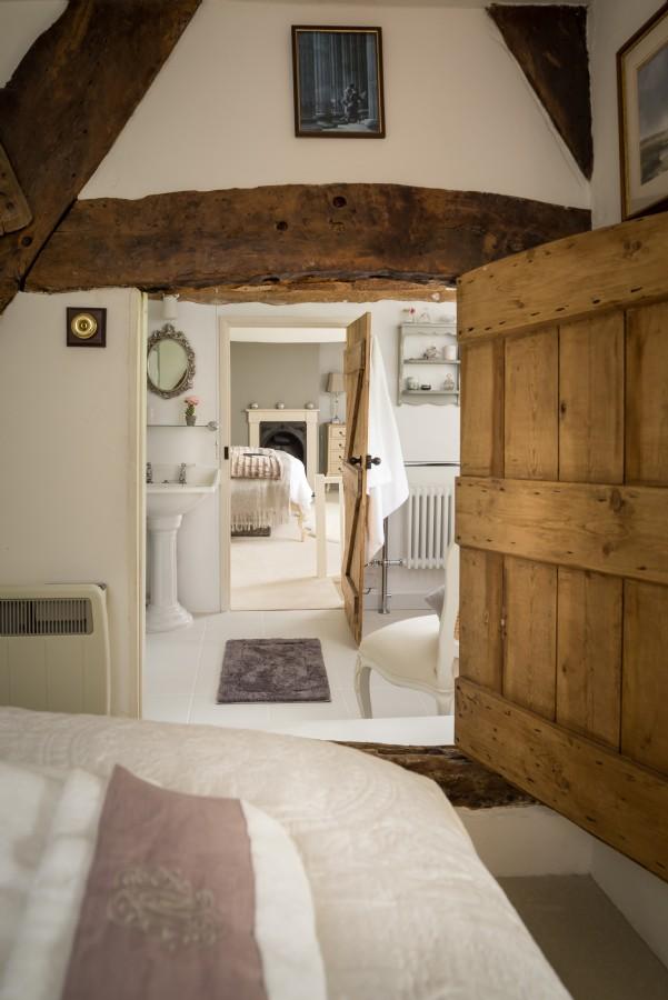 Η ξύλινη πόρτα του υπνοδωματίου οδηγεί στο μπάνιο και από εκεί στο άλλο υπνοδωμάτιο
